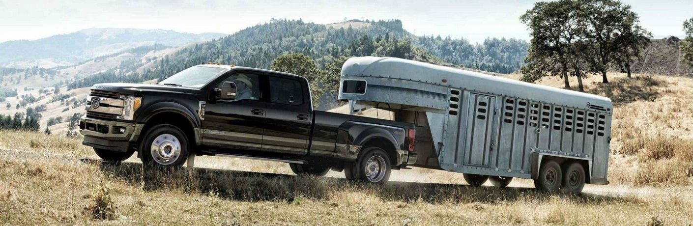 side view of a black 2020 Ford F-450 Super Duty pulling a horse trailer