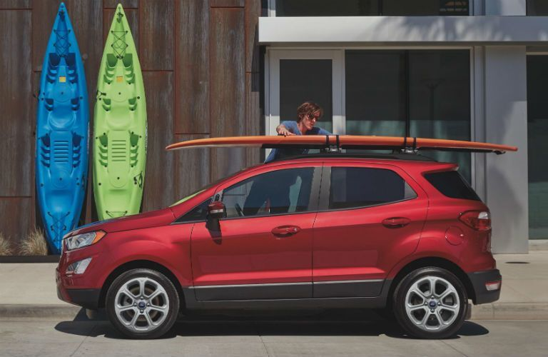 side view of a red 2021 Ford EcoSport with a surfboard on its roof rack