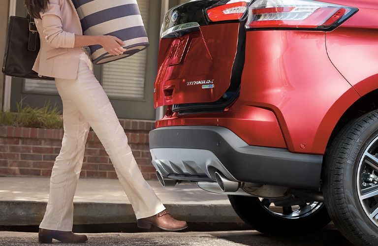 woman using foot activated tailgate of a red 2021 Ford Edge ST-Line