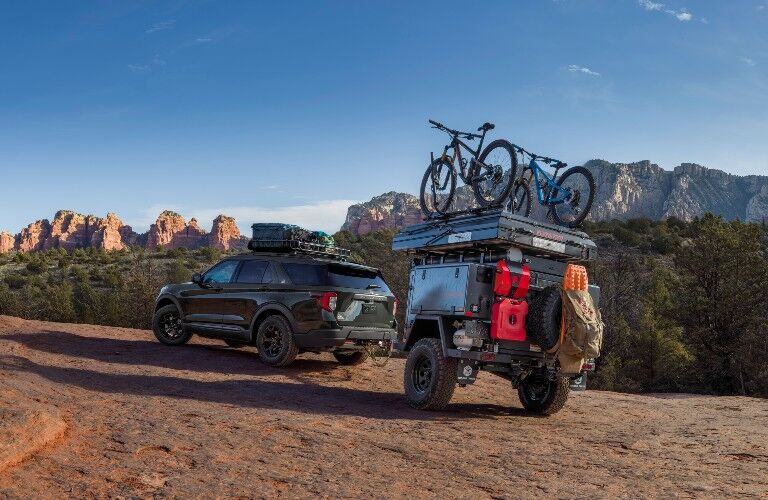 rear view of a green 2021 Ford Explorer Timberline towing a camper and bikes