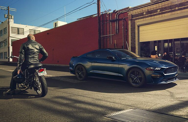 2021 Ford Mustang parked with a man on a bike watching
