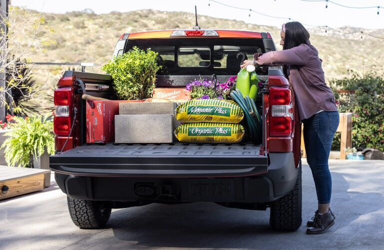woman loading the cargo bed of her red 2022 Ford Maverick
