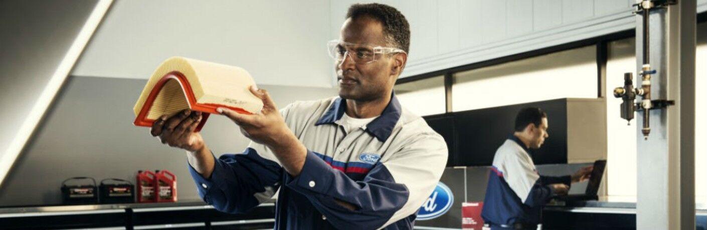 Ford tech examining a filter