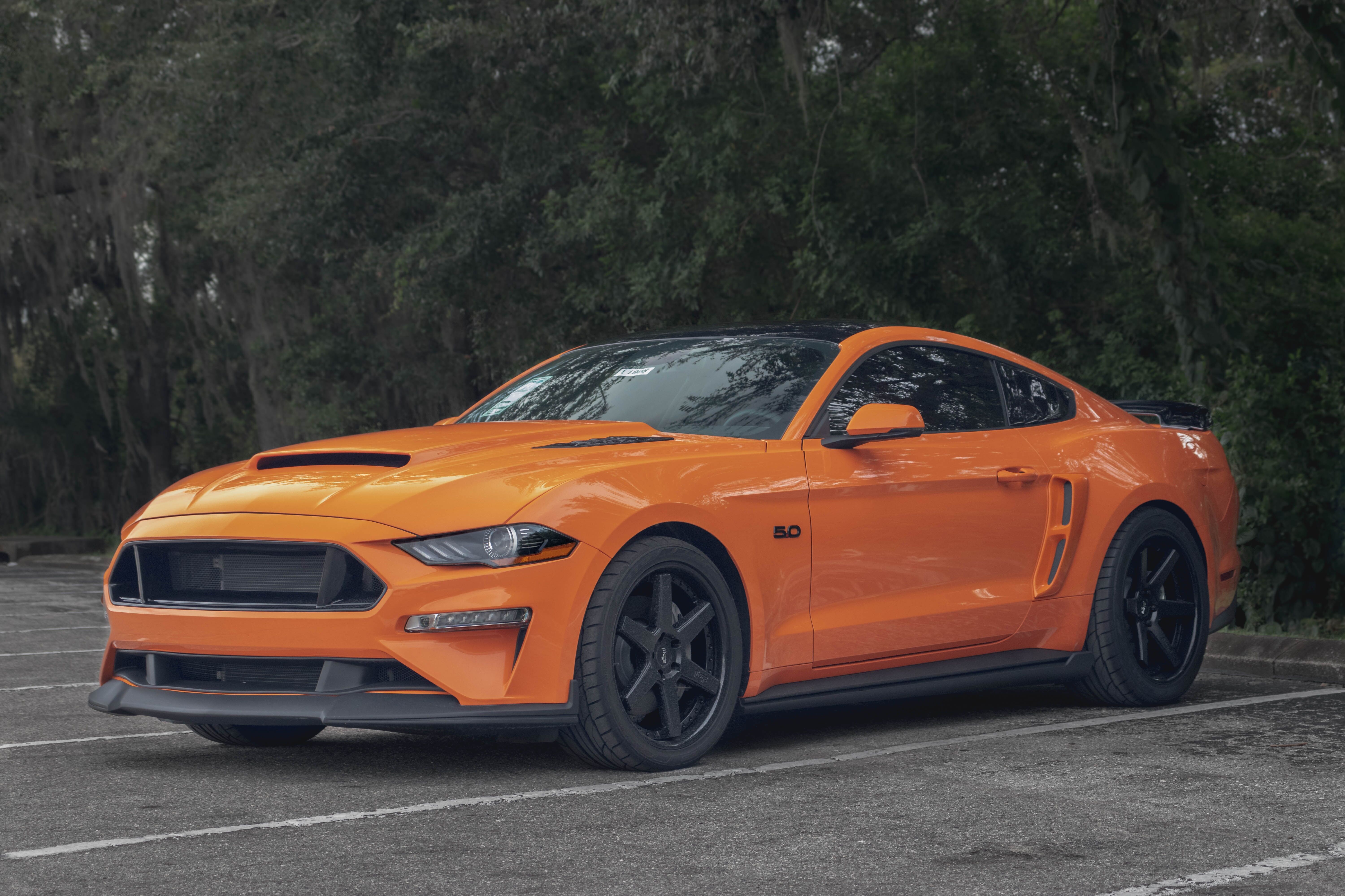 side view of an orange Ford Mustang