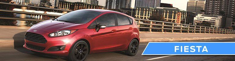 side view of a red Ford Fiesta Hatchback driving down the highway