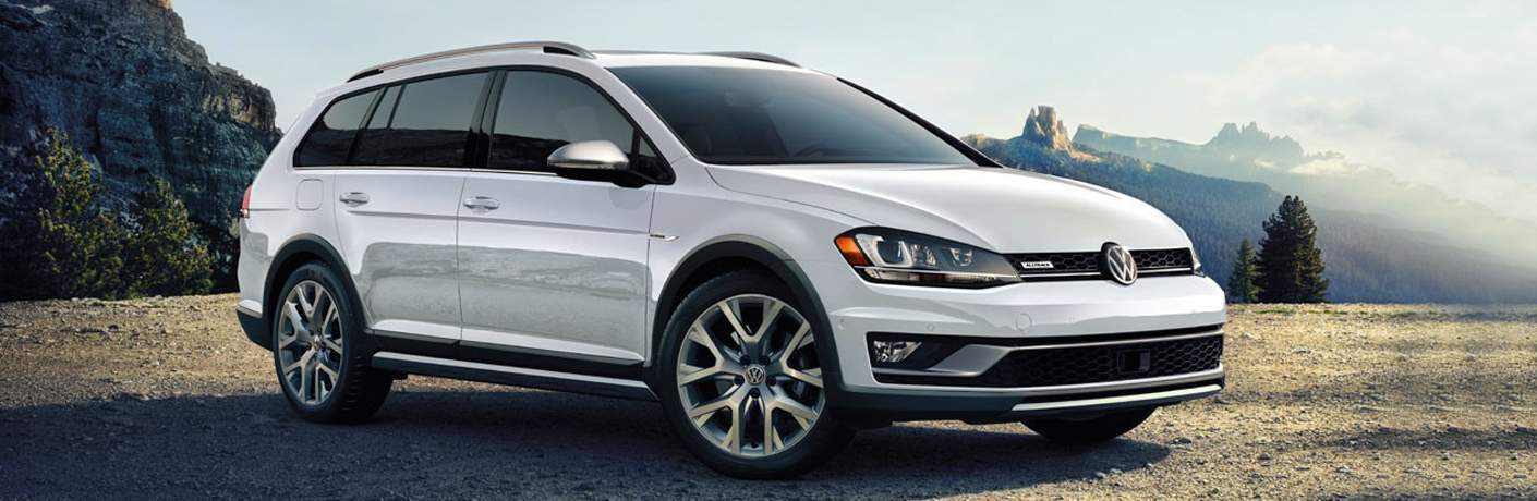 white 2018 VW Golf Alltrack exterior front passenger side with mountains in the background