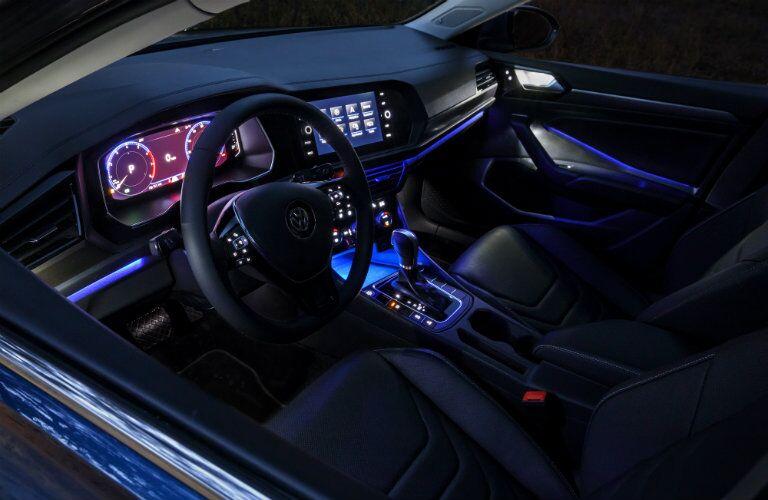 Black interior of the 2019 Volkswagen Jetta with blue ambient lighting