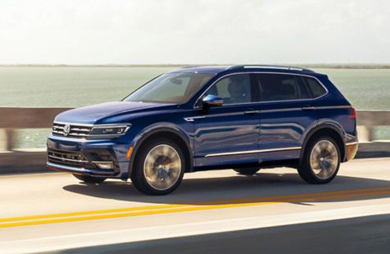 A blue-colored 2021 Volkswagen Tiguan driving on a road with a body of water in the background