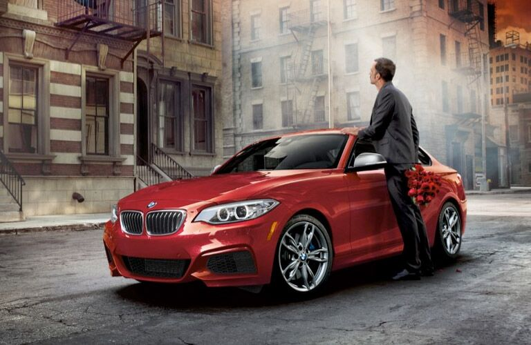 Man Next to a Red 2017 BMW 2 Series Coupe on a City Street