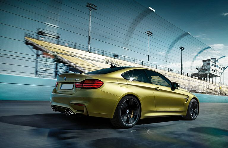 Gold 2017 BMW M4 Coupe Rear Exterior on the Track