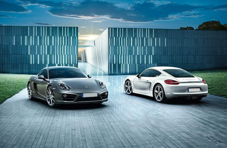 Gray and White 2016 Porsche Cayman Models Parked in Front of Modern Building