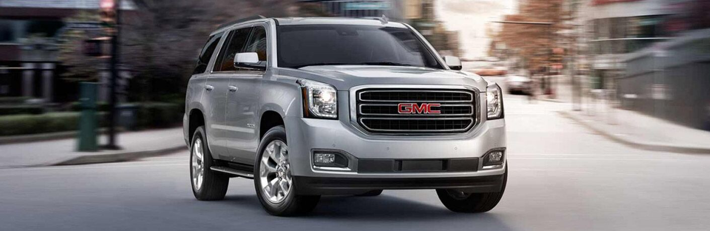 Silver 2017 GMC Yukon Driving on a City Street