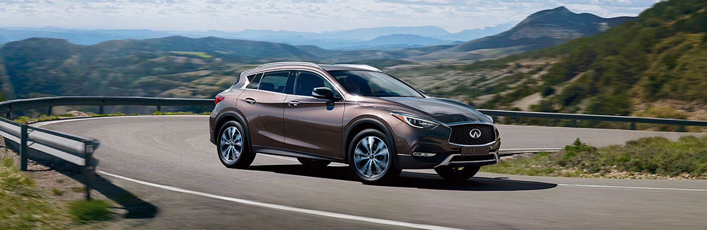 2017 INFINITI QX30 exterior front fascia and passenger side on mountain road