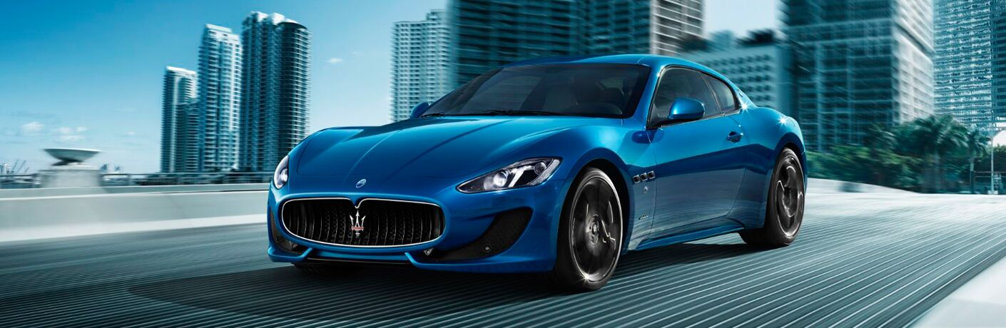 Blue 2017 Maserati GranTurismo on a City Freeway with a City Skyline in the Background