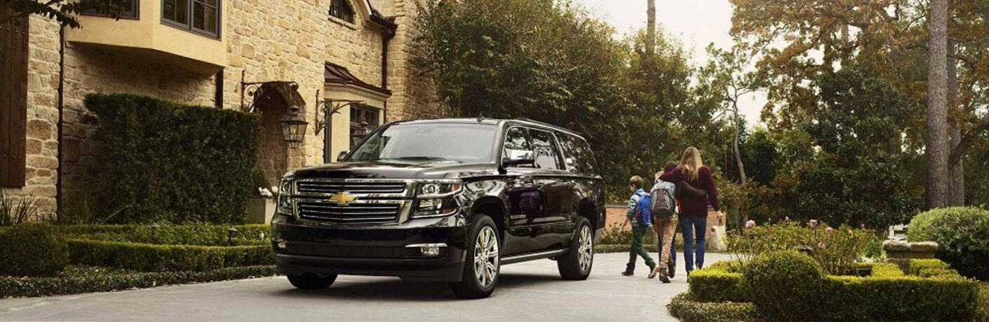 Family walking towards black Chevrolet Suburban