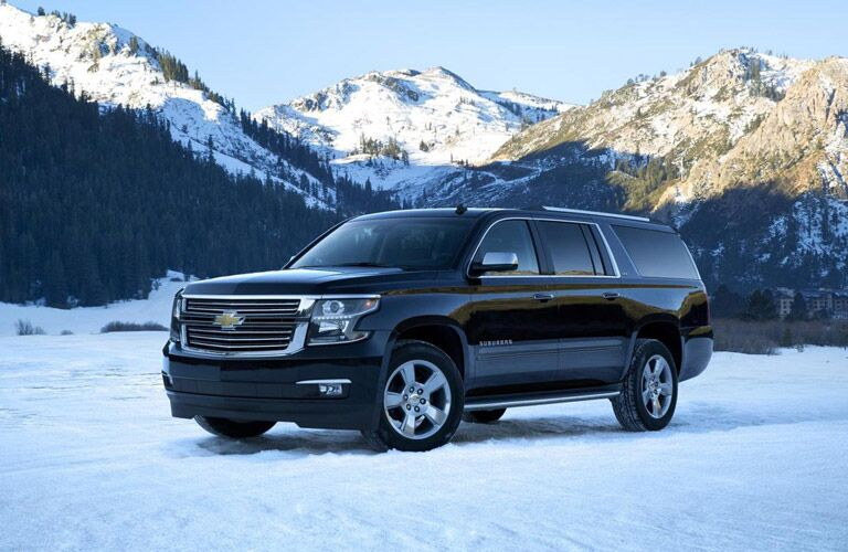 Chevrolet Suburban parked with snow-capped mountain peaks in background
