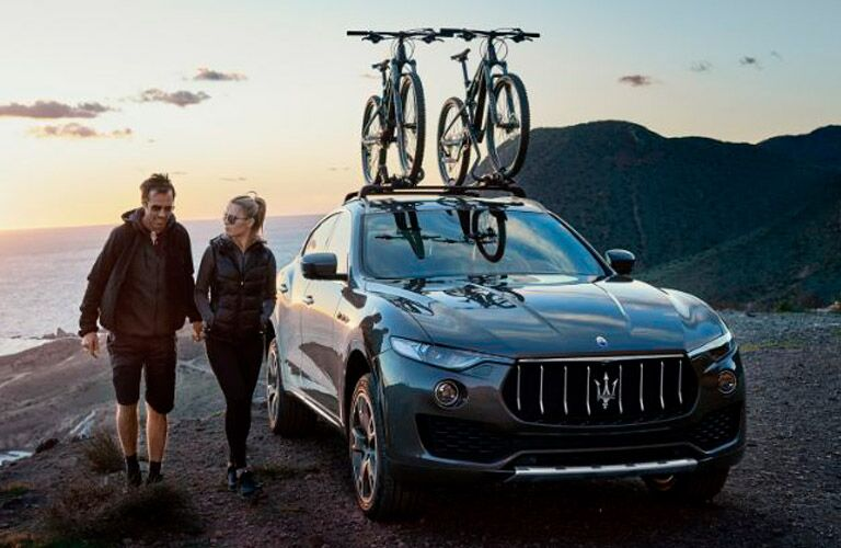 Black 2018 Maserati Levante GranLusso with Bike Rack next to young couple on beach overlook at sunset