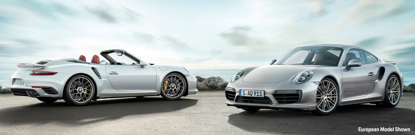 White Convertible and Silver Coupe 2018 Porsche 911 Turbo Next to the Water