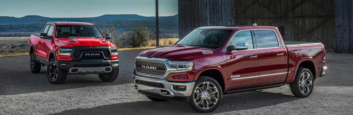Red 2019 Ram 1500 Rebel and Maroon 2019 Ram 1500 Limited at a Farm