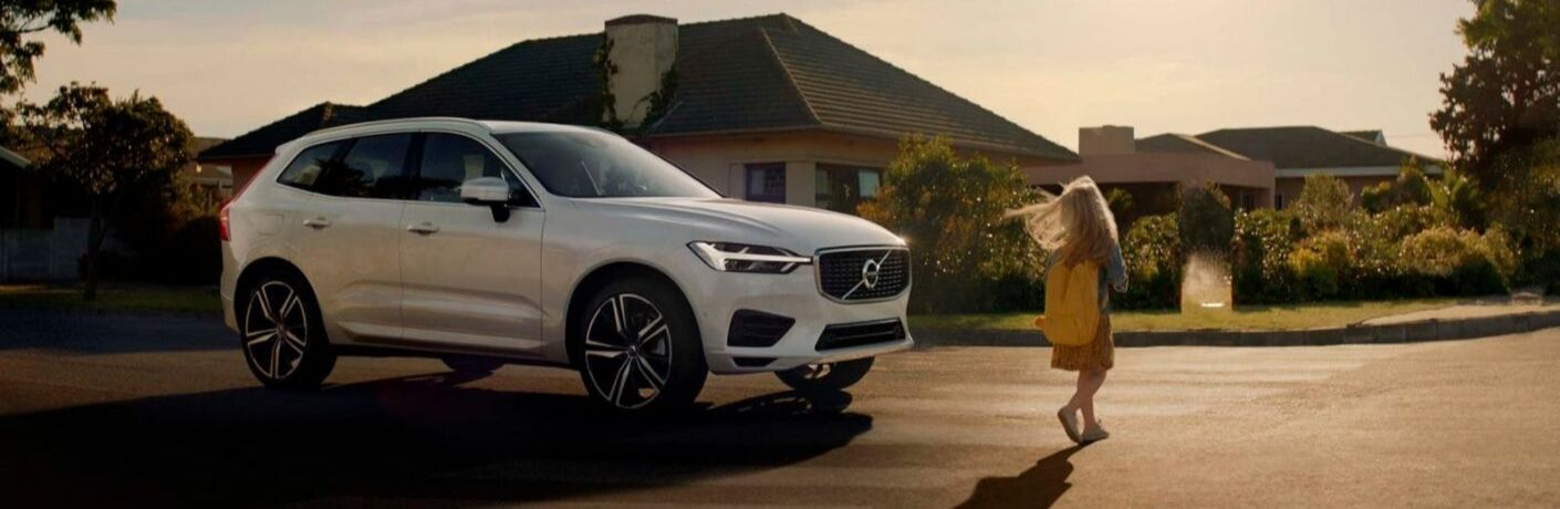 White 2019 Volvo XC60 and Little Girl in a Driveway