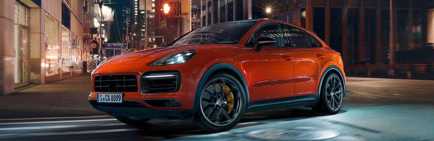 Orange 2020 Porsche Cayenne Coupe on a City Street at Night