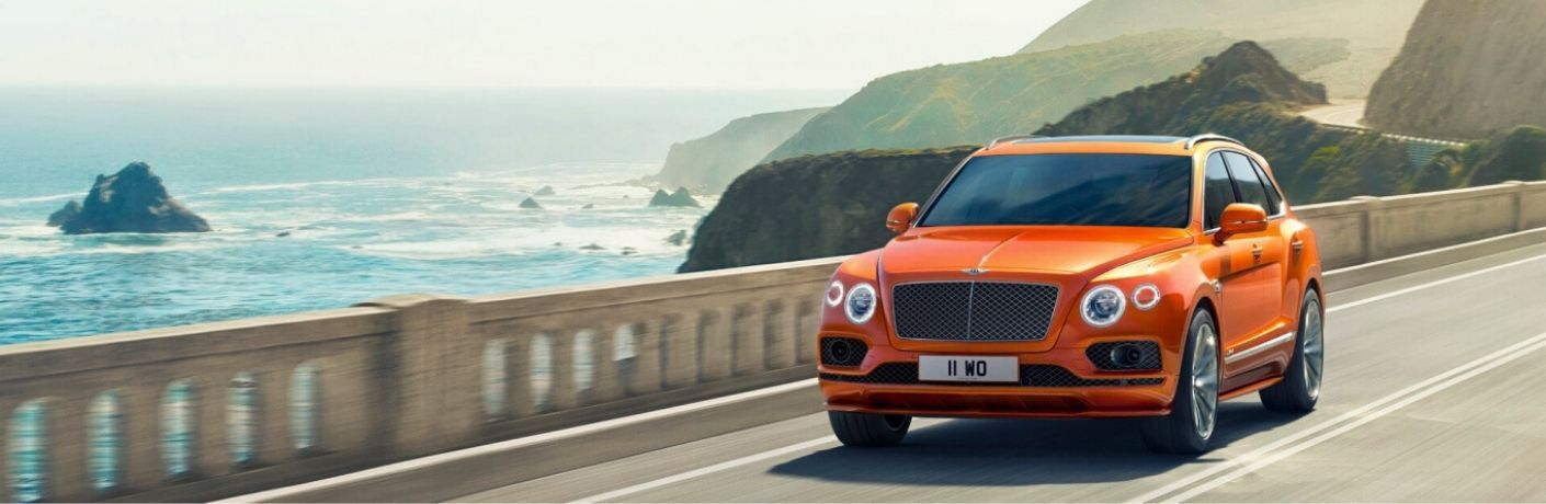 Orange 2020 Bentley Bentayga on a Bridge