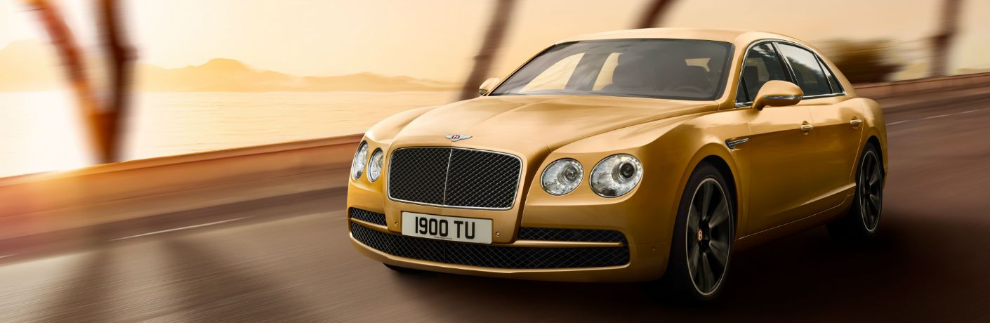 Gold 2018 Bentley Flying Spur Driving on a Coast Road at Sunset