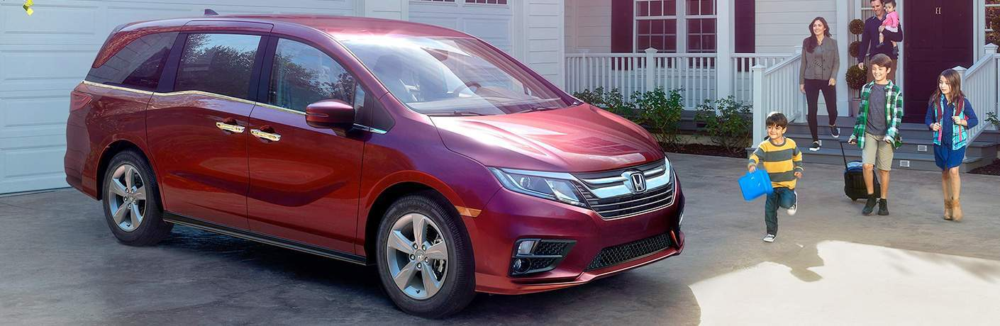Red 2018 Honda Odyssey parked in front of garage with family walking toward it