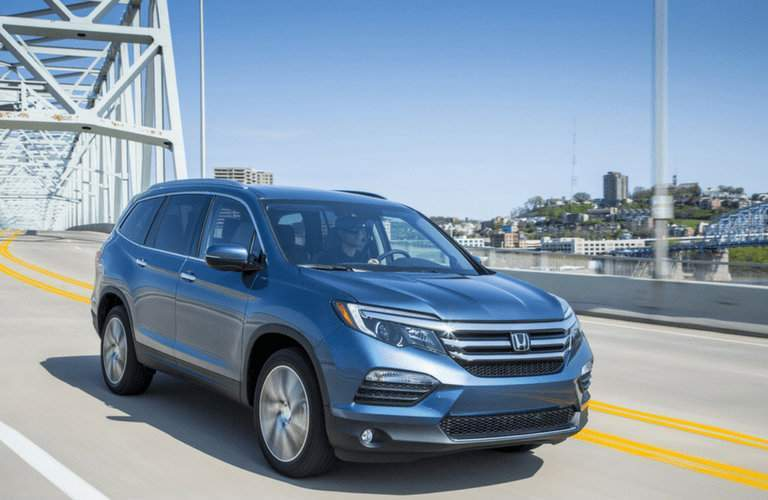 Blue 2018 Honda Pilot driving through bridge