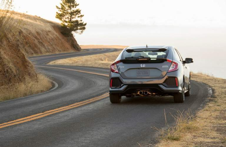 Rear end of the 2018 Honda Civic Hatchback driving down coastal highway