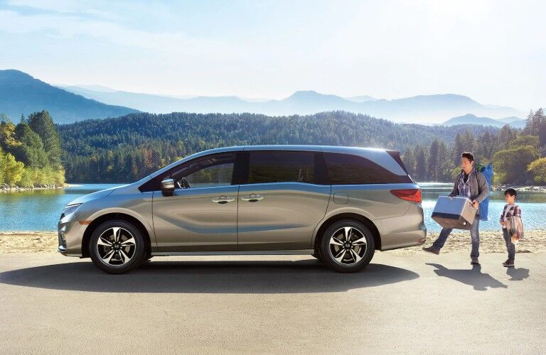 Driver angle of a silver 2020 Honda Odyssey parked by a lake with a dad and son using the power tailgate