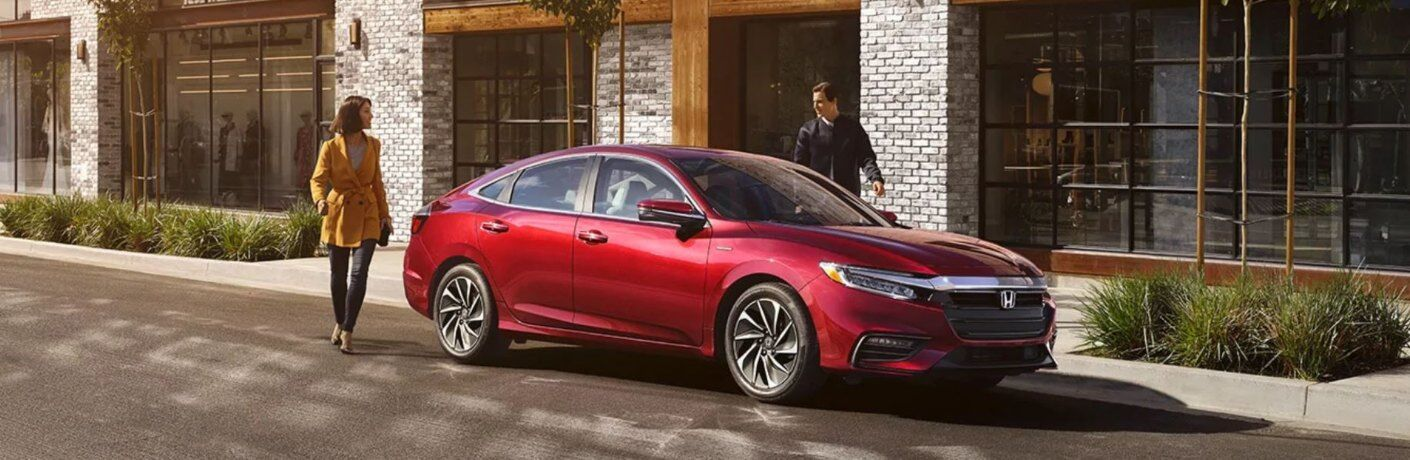 Couple walking beside red 2020 Honda Insight