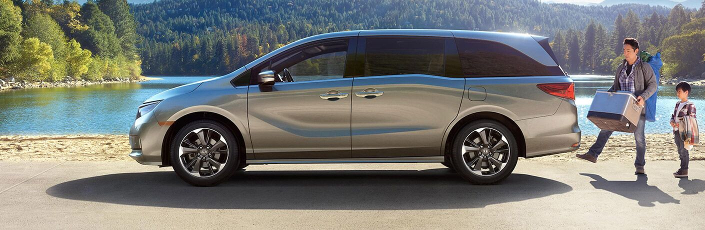 2021 Honda Odyssey driver side parked on forest beach father and son walking to tailgate