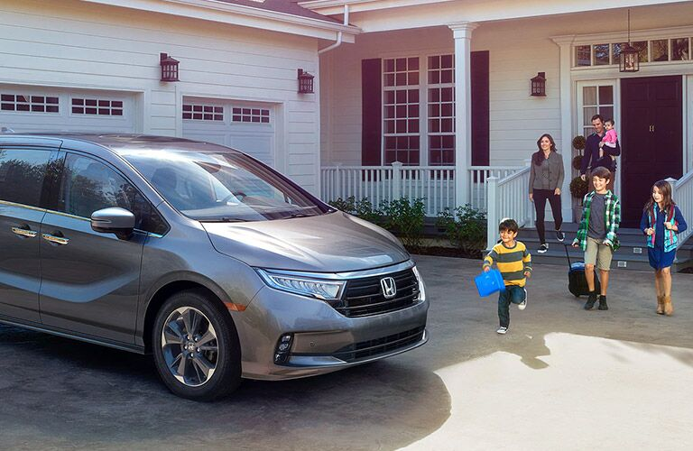 2021 Honda Odyssey grey exterior front fascia parked in driveway family walking out of house