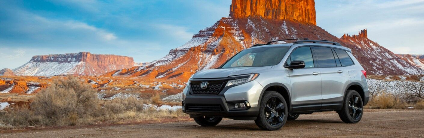 2021 Honda Passport silver parked in front of snow on rock formation