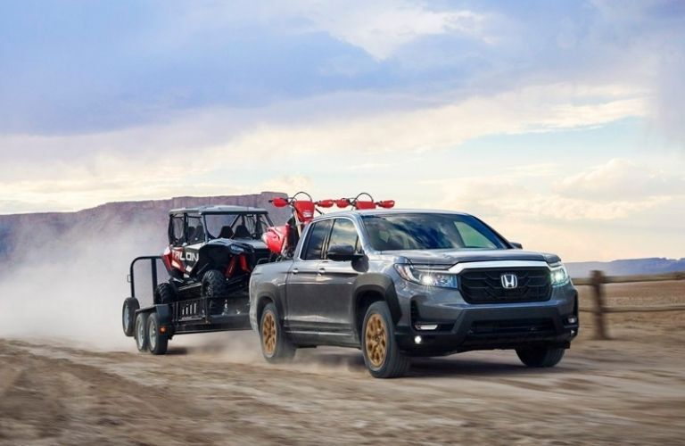 2021 Honda Ridgeline towing a trailer with a vehicle in it