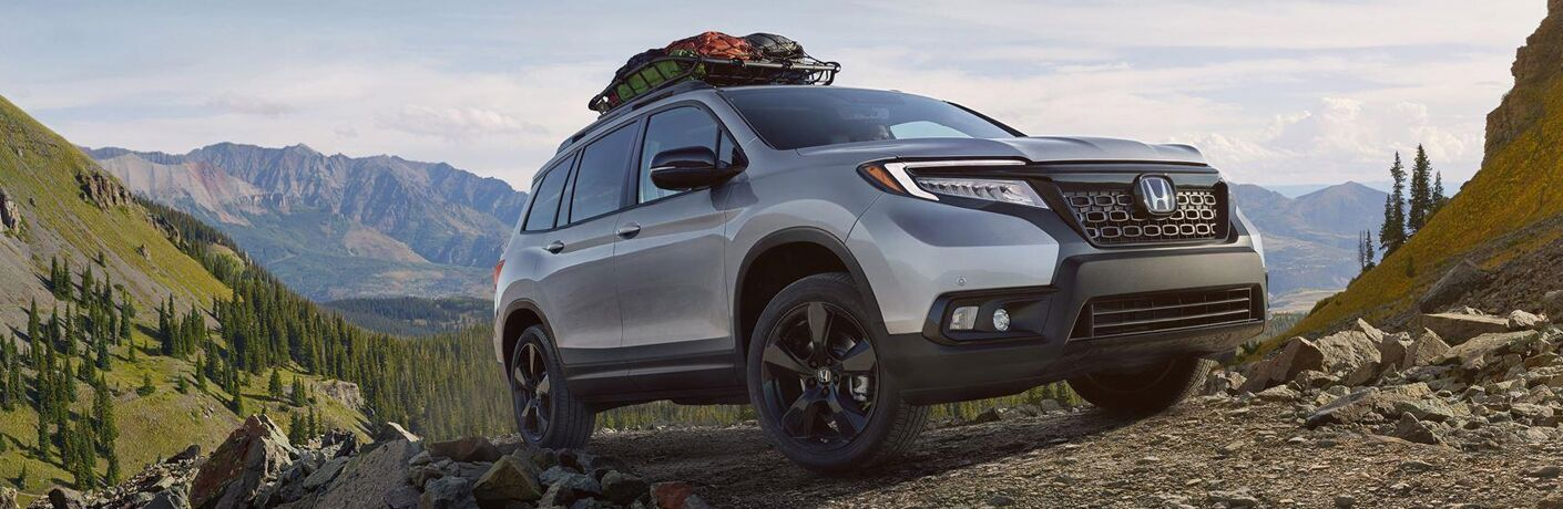2019 Honda Passport exterior front fascia and passenger side on mountain road with cargo on roof