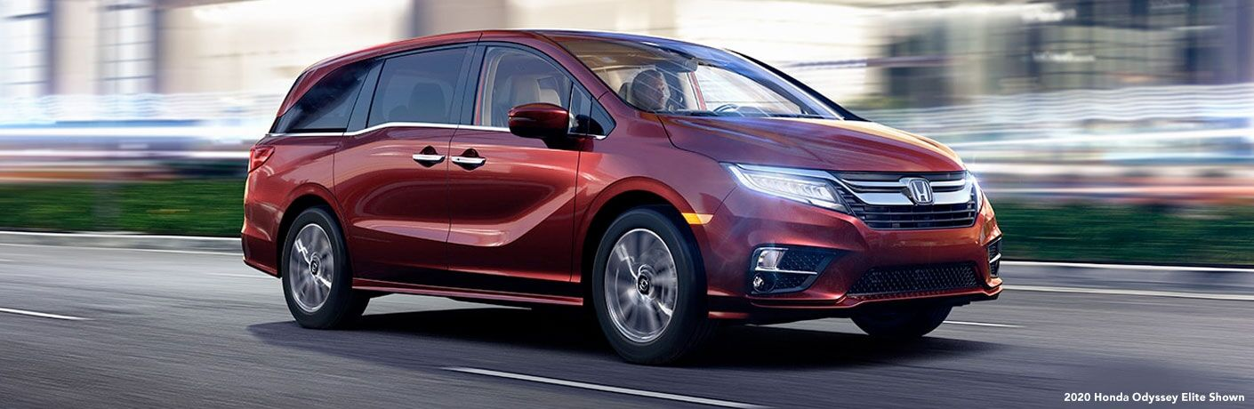 Red 2020 Honda Odyssey driving down road from exterior front passenger side view