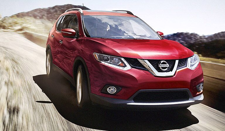 Red Nissan Rogue on the back roads
