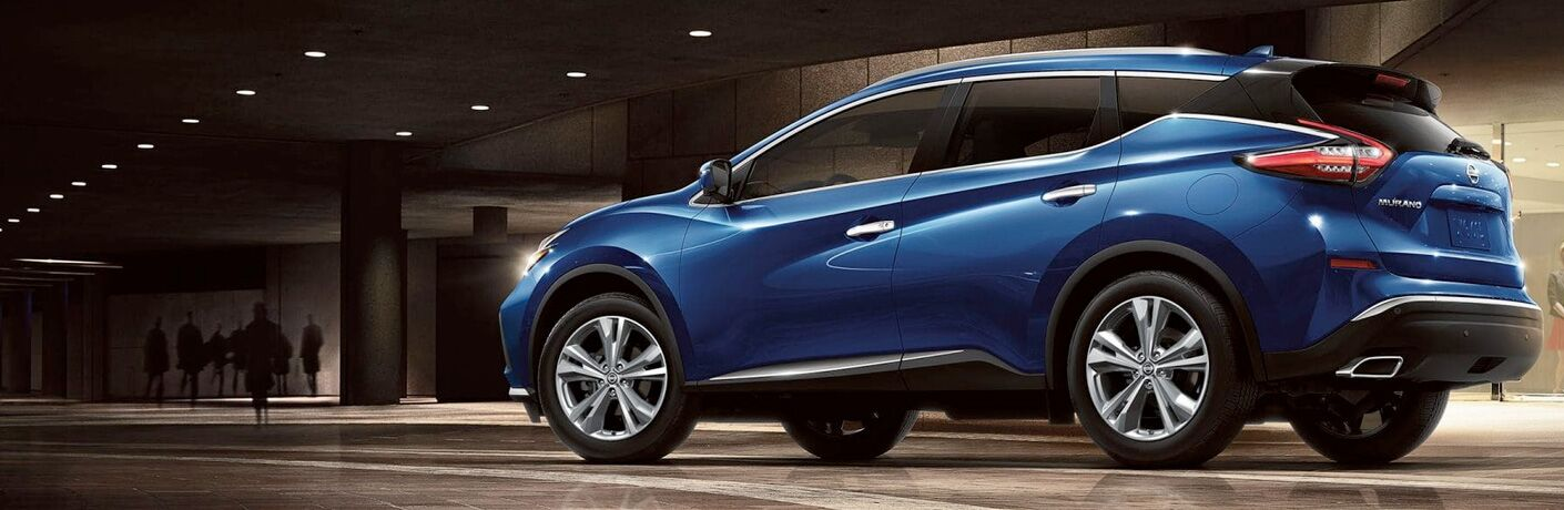 2019 Nissan Murano exterior back fascia and drivers side inside concrete building with shadowy figures in front of vehicle