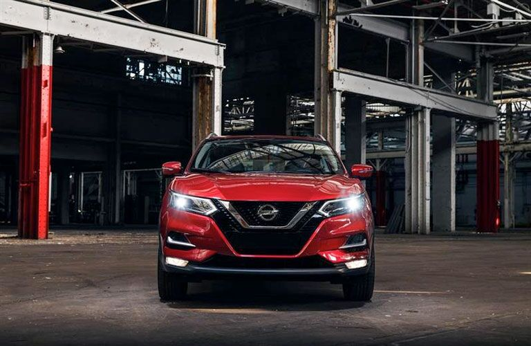 2020 Nissan Rogue red parked at construction site facing shot head on