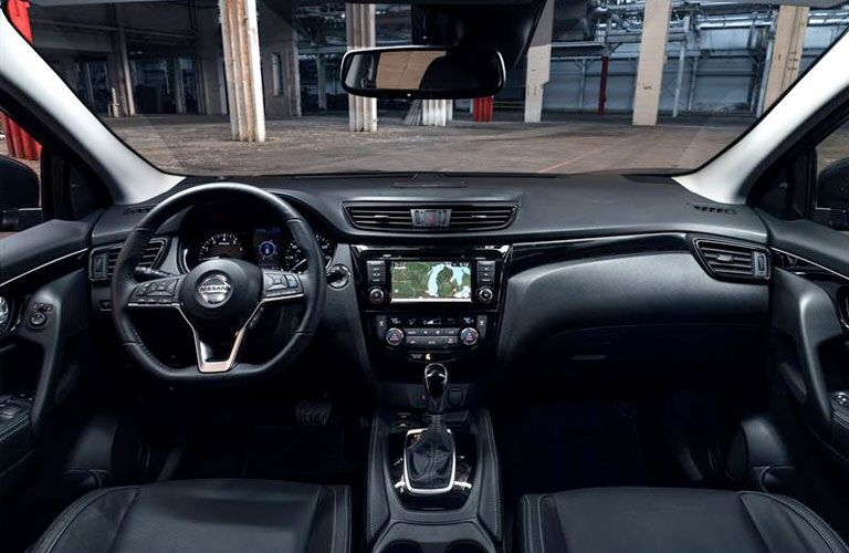 2020 Nissan Rogue Sport interior front cabin steering wheel and dashboard in parking garage