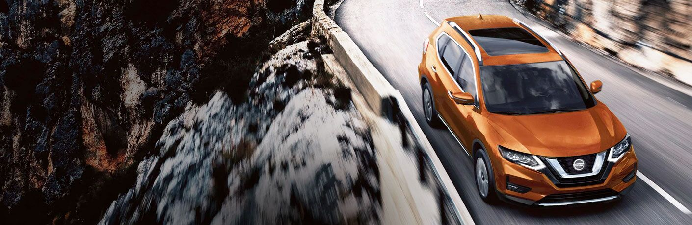 2020 Nissan Rogue orange driving on narrow mountain row with cliff and rails in shot_o