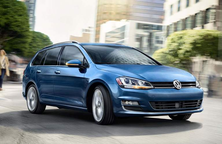 blue volkswagen golf sportwagen driving in city