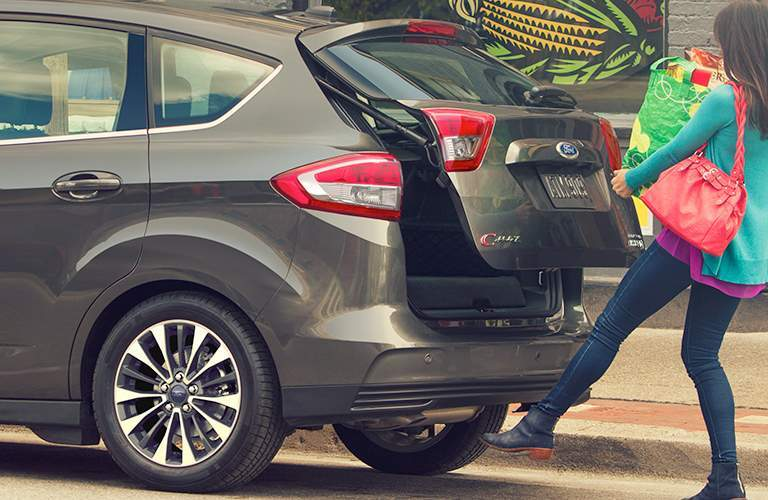 woman with her hands full using her foot to activate the power lift gate of a 2018 Ford C-MAX Hybrid