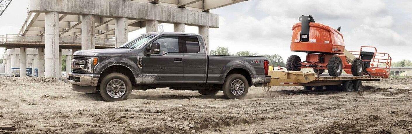side view of a gray 2018 Ford F-350 Super Duty towing a large piece of construction equipment at a construction site
