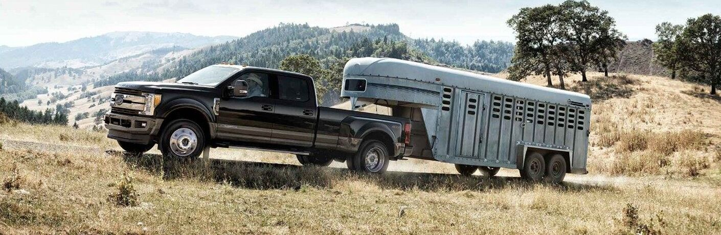 side view of a black 2018 Ford F-450 Super Duty towing a horse trailer along a dirt road