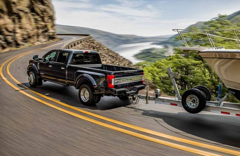 side view of a black 2018 Ford F-450 Super Duty towing a boat along a winding highway
