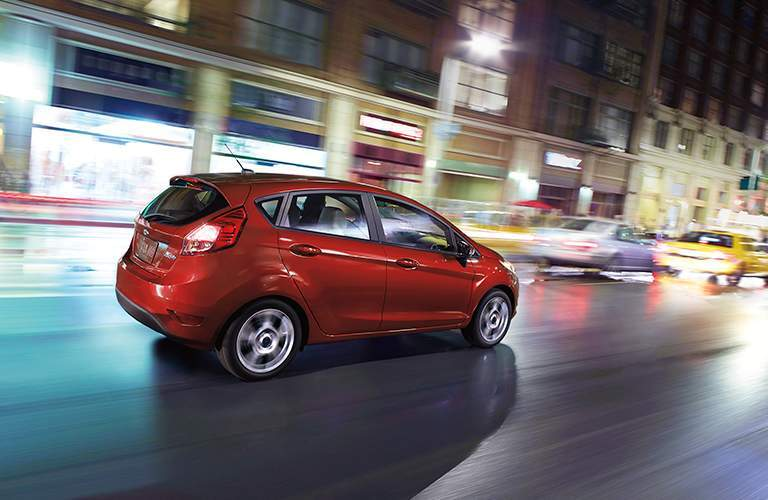 side view of a red 2018 Ford Fiesta Hatchback driving down a city street