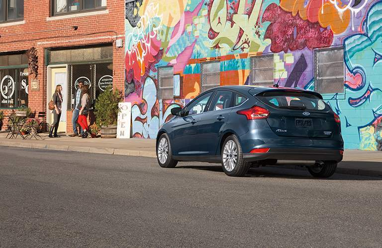 rear view of a blue 2018 Ford Focus Hatchback parked next to a graffiti covered wall
